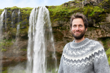 Man in Icelandic sweater by waterfall on Iceland