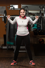 Young Woman Doing Exercise Barbell Squat