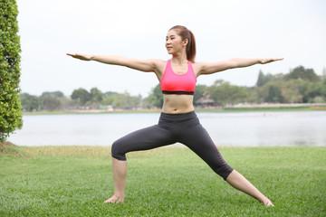 Yoga virabhadrasana II warrior pose by woman on lawn,left side