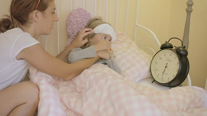 Little girl sick in bed with mother checking time