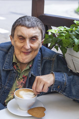 Disabled man with cerebral palsy sitting and drinking coffee.