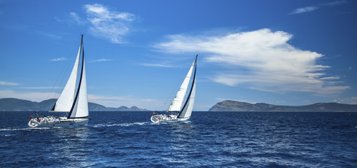 Panorama of the yacht race in the open sea. Luxury yachts.