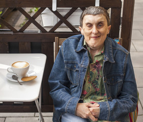 Disabled man with cerebral palsy sitting at outdoor cafe.