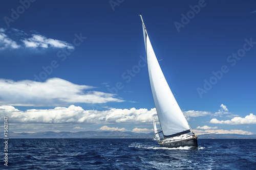 Ship yachts with white sails in the open Sea. Luxury boats.