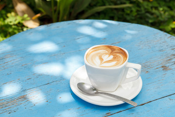 Cup of latte coffee on blue wooden table