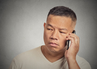 headshot upset sad depressed man worker talking on mobile phone