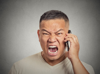 Angry middle aged man employee shouting while on phone