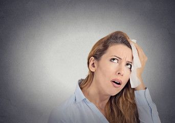 tired worried woman wipes sweat on her face grey background