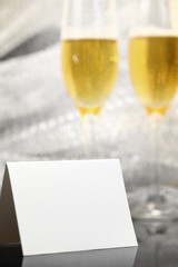 Card with two glasses of champagne and silver bokeh background
