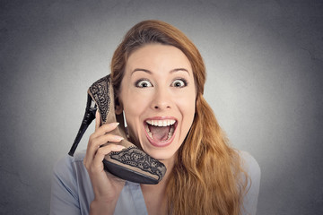 Headshot happy woman excited holding high heeled shoe as phone