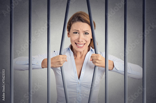 Stressed desperate angry woman bending bars of her prison - 75623353