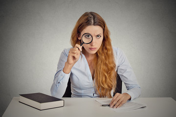 woman with glasses skeptically looking through magnifying glass