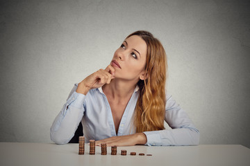 woman executive sitting at table with growing stack of coins