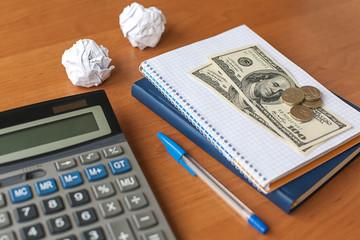 business desktop with calculator, notebook, money