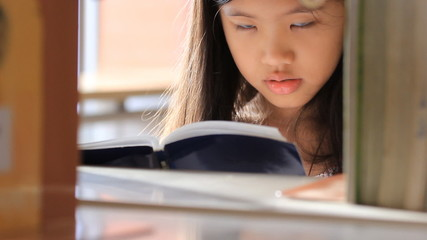 Little Asian girl reading a book in library, tilt up camera