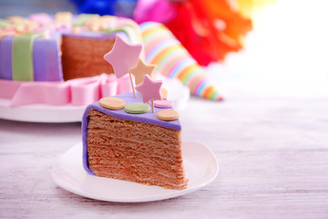 Delicious piece of birthday cake on table on bright background