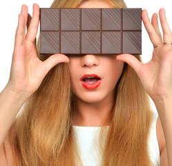 Beautiful girl hide her eyes with chocolate bar studio shot