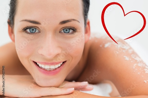 Peaceful brunette lying with salt scrub on back - 75625948