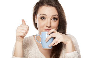 young woman drinking from a cup and showing thumbs up