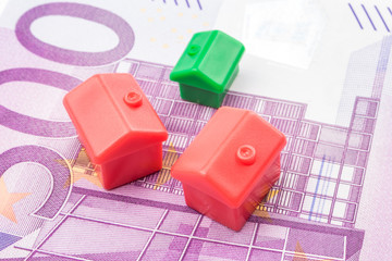 Three little houses made of plastic laying on 500 euro banknote