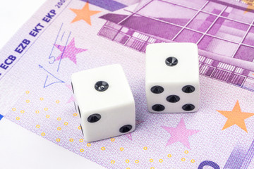 Two white dices with black dots are laying on 500 euro banknote