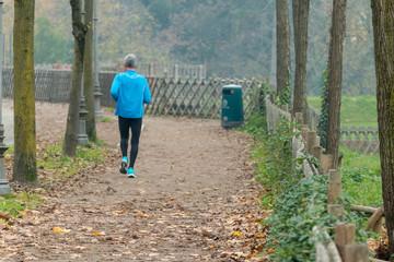Elderly man jogging in park in autumn
