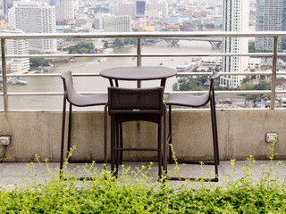 Rattan oone table with two stool chairs standing against the ter