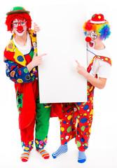 fröhliche clowns zeigen auf werbeplakat