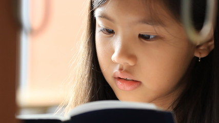 Close up little Asian girl reading a book in library, pan camera