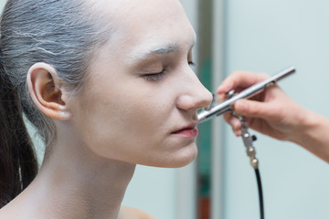The process of putting airbrush make up.