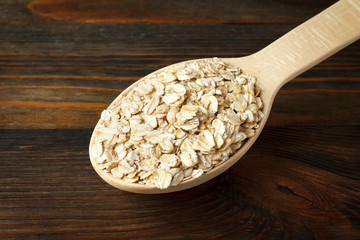 Rolled oats in a wooden spoon on wood