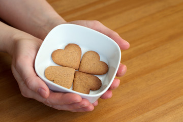 Female's hands holding white bowl with cookies