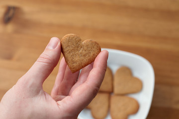 Female hand holding heart-shaped cookie