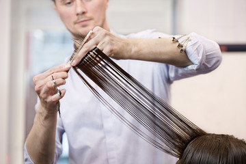 Hairdresser making a haircut for a brunette girl
