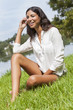 Latina Woman Girl Sitting On Grass by Lake in Summer