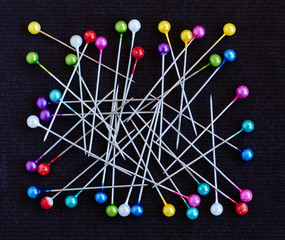 Multicolored pins over black background