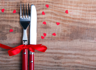 Knife and fork and little red hearts on the wooden table.