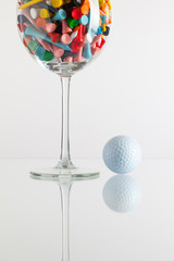 Glass of wine and golf equipments