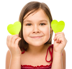 Little girl is holding hearts near her eyes