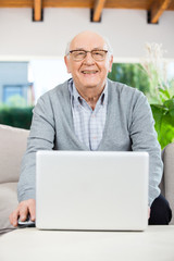 Happy Senior Man With Laptop At Nursing Home Porch