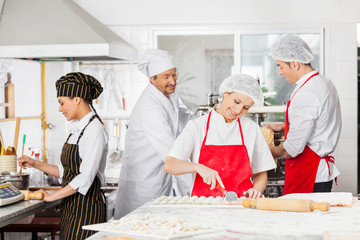Chefs Preparing Pasta In Kitchen