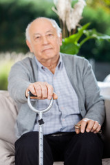 Portrait Of Elderly Man Holding Metal Cane