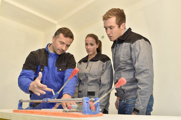 Teacher with students using ceramic saw