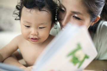 Mother reading to her baby boy.
