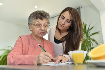 Young woman visiting elderly woman in nursing home