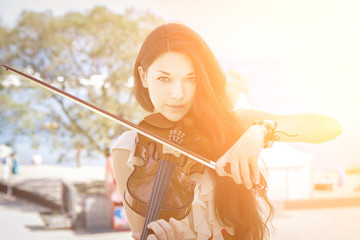 Portrait of a young female playing the violin. With sunshine.