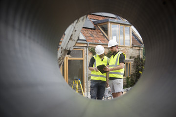 Two construction workers at a building site, viewed through a round pipe.