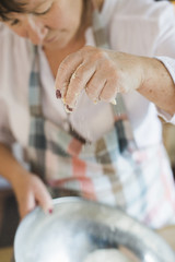 A woman measuring and sifting white flour, making a crumble topping. Home baking.