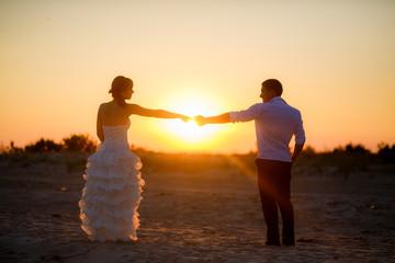 happy newlyweds at sunset