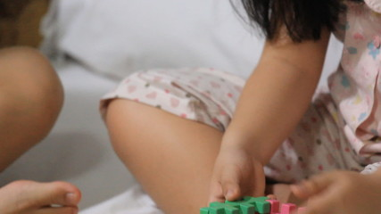 Little Asian Children Playing With Blocks On The Bed Together